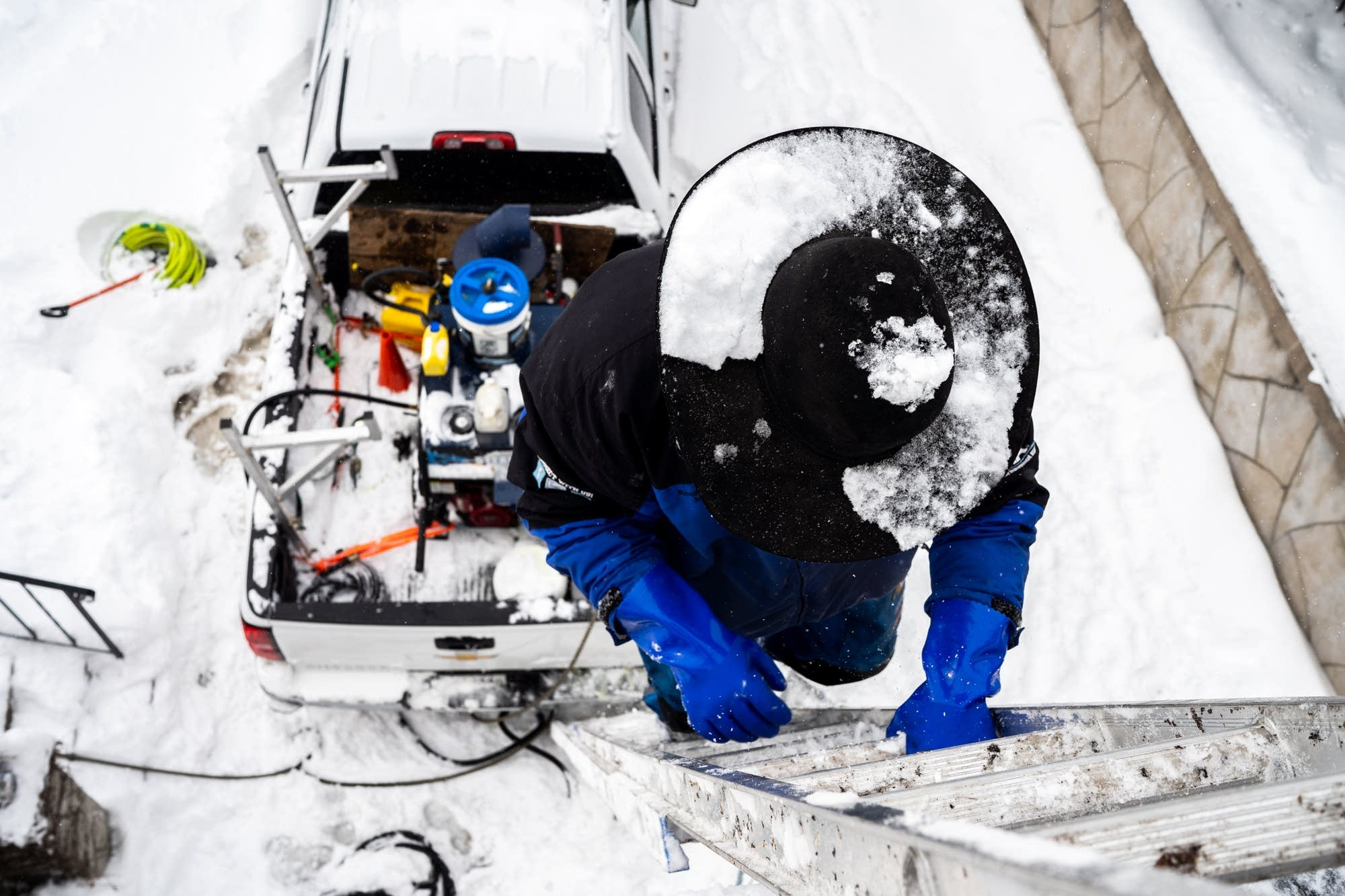 Snow falls on Jake Weber's cowboy hat as he climbs a ladder.