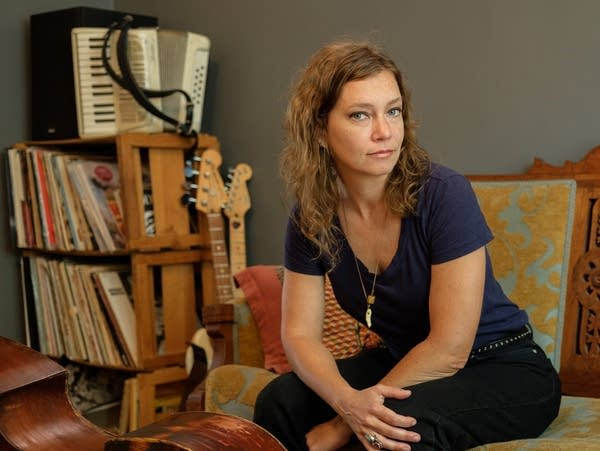 Liz Draper sitting on couch near musical instruments.