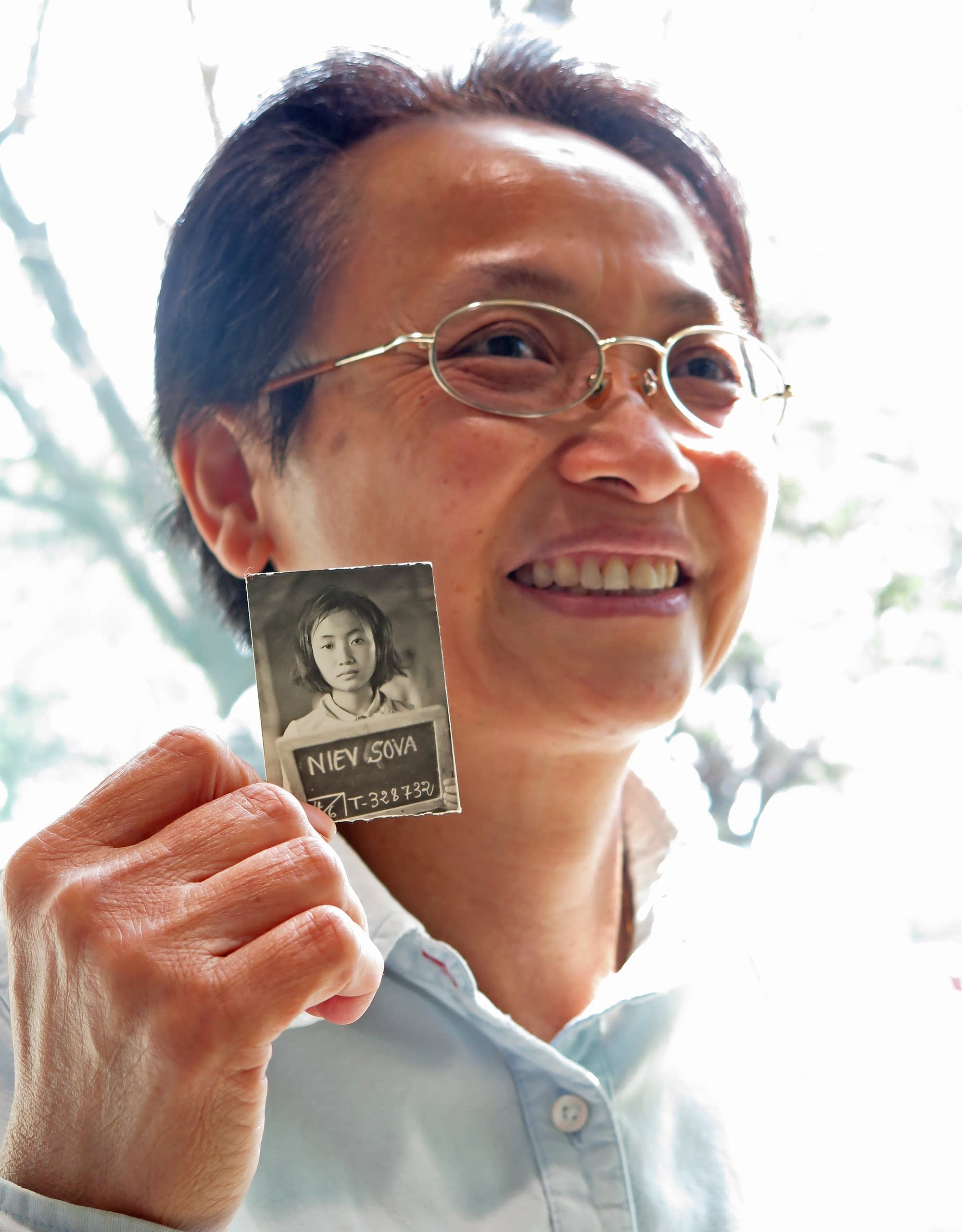 Sova Niev holds her identification photo.