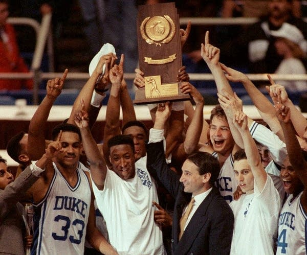 Coach Mike Krzyzewski and his Duke team celebrate April 7, 1992 in Minneapolis, after receiving their championship trophy. Duke beat Michigan 71-51 to become the first team to repeat as national champions since 1973. (AP Photo/Jim Mone)