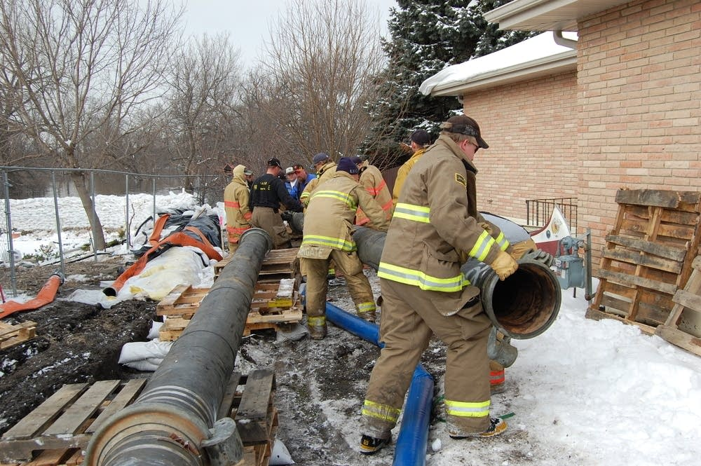 Firefighters work to install pipe for a new pump