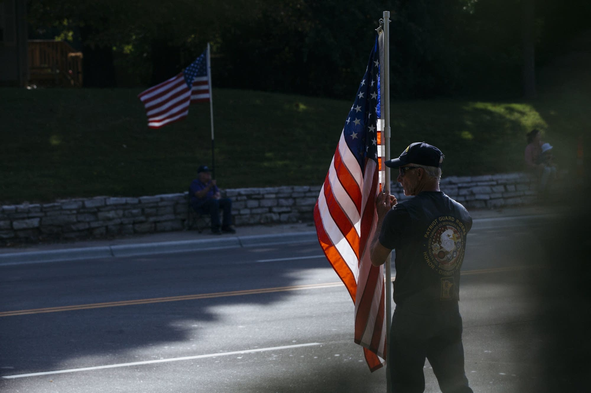 A member of the Patriot Guard Riders holds a flag on Highway 101.