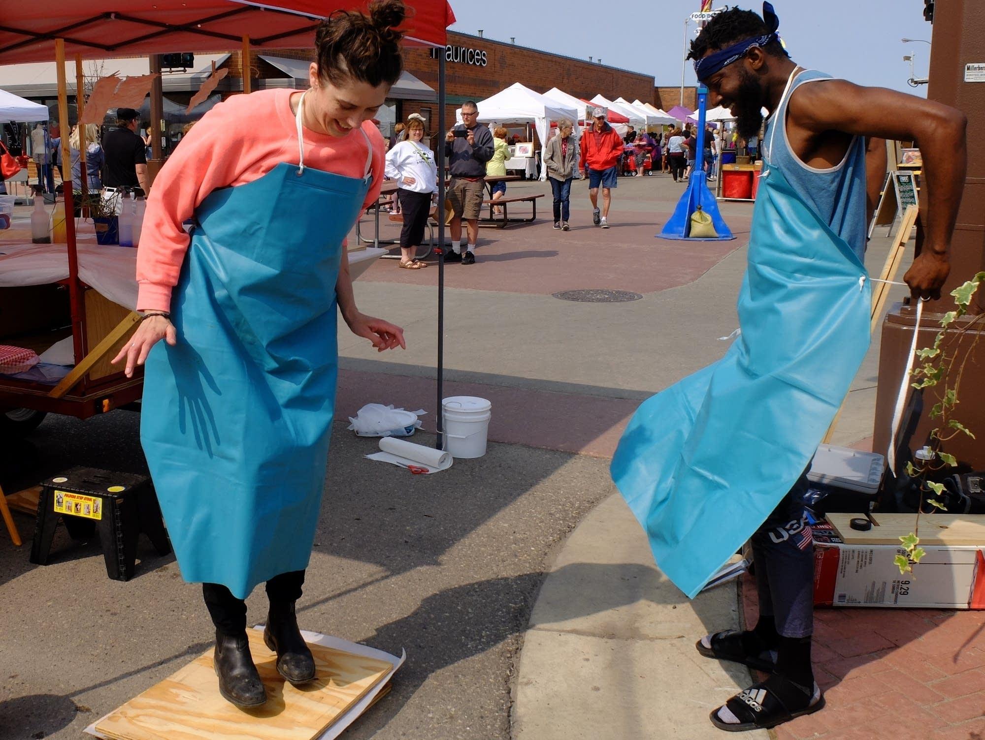 Anna Haglin jumps on a makeshift press while Franklin Ugochukwu watches.