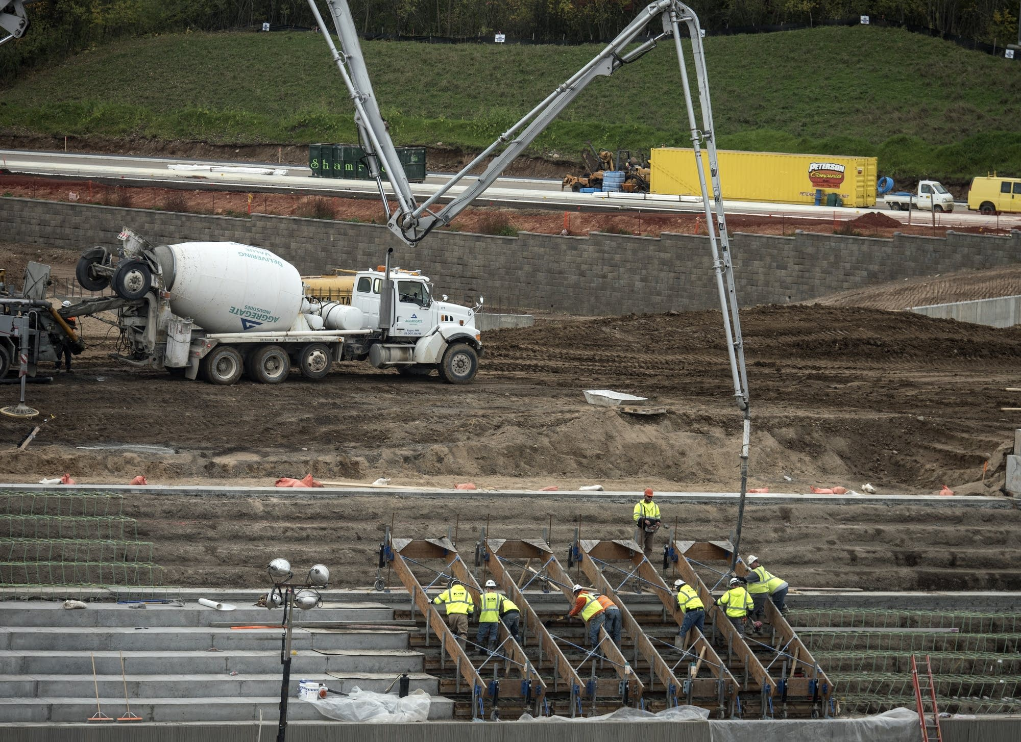 Workers pour concrete in the seating area of the outdoor stadium.