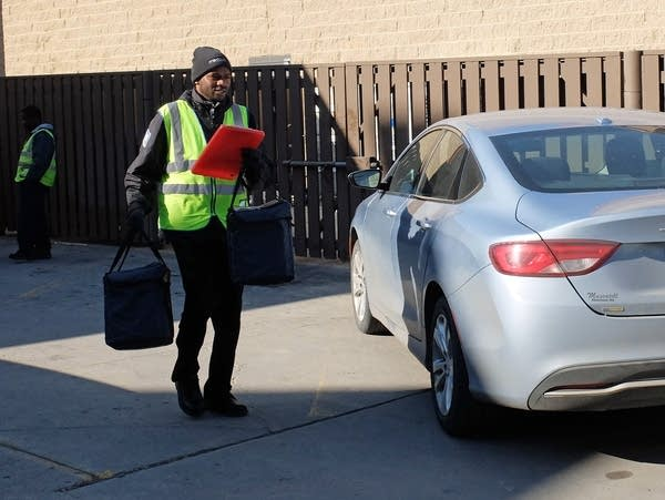 a man carries a cooler and a clipboard across a parking lot