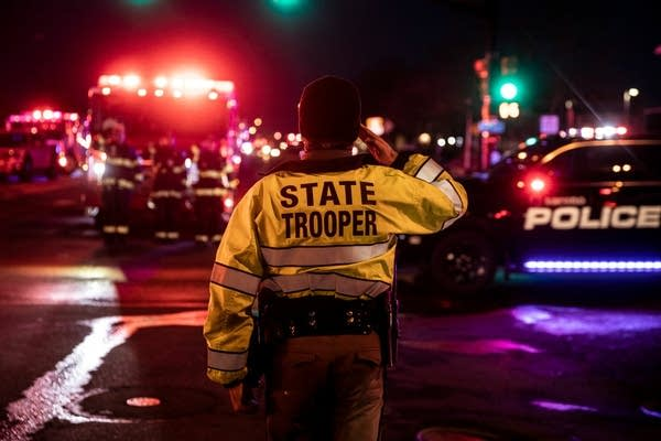 A Colorado State Police officer salutes as a procession drives by.