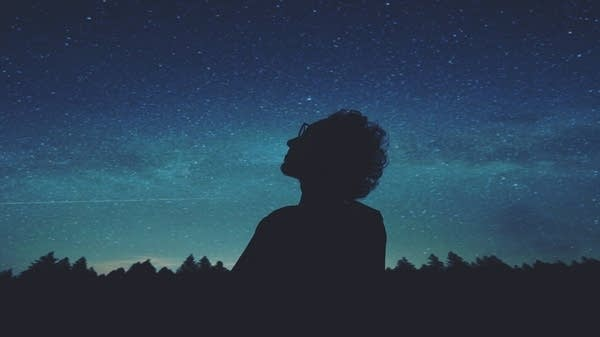 A person contemplates a starry sky.