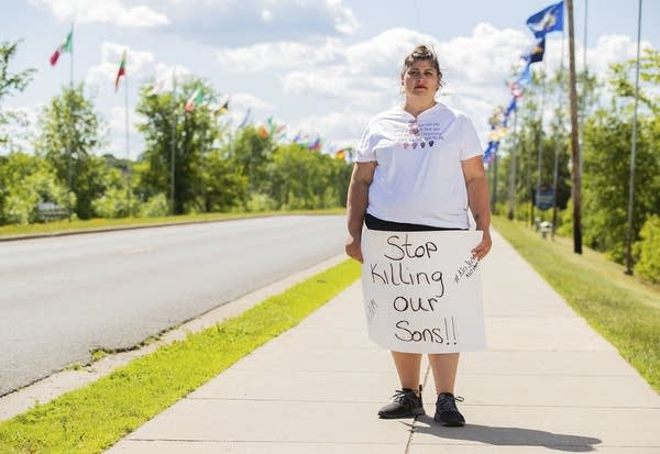"""A person holds sign that reads """"Stop killing our sons!"""""""