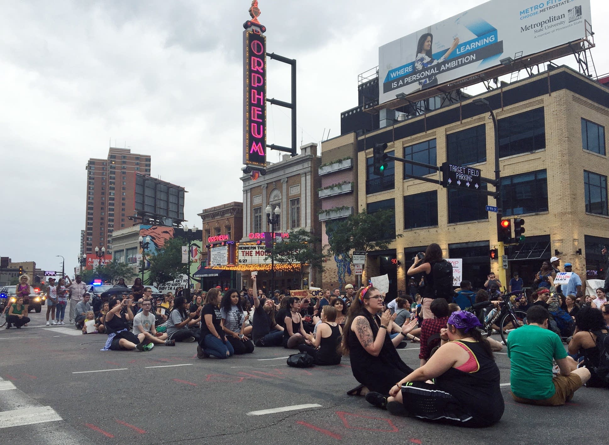 About 50 protesters sit in street at 9th and Hennepin Ave.
