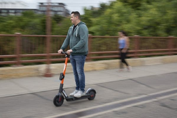 A man wearing a sweatshirt rides an orange electric scooter.