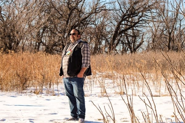 A man stands outside on a snow-covered field.