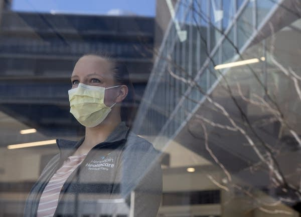 A woman wearing a face mask stands behind a window