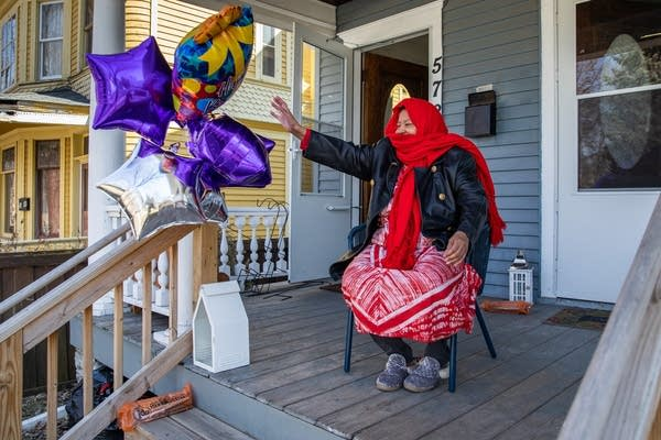 A woman in red waves from a porch with balloons.