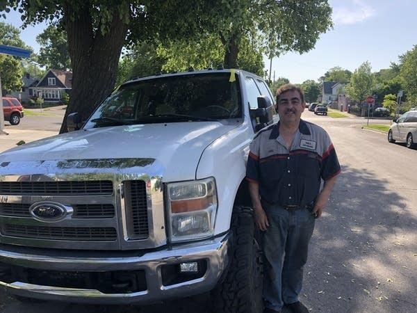 A man stands next to a truck.