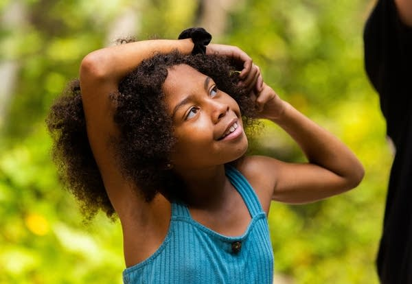 A young girl looks up with her hands on her head.