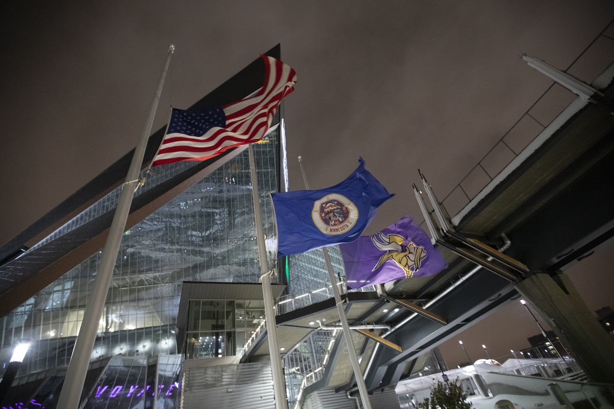 Flags blow in 20 mph winds and snow falls onto Minneapolis.