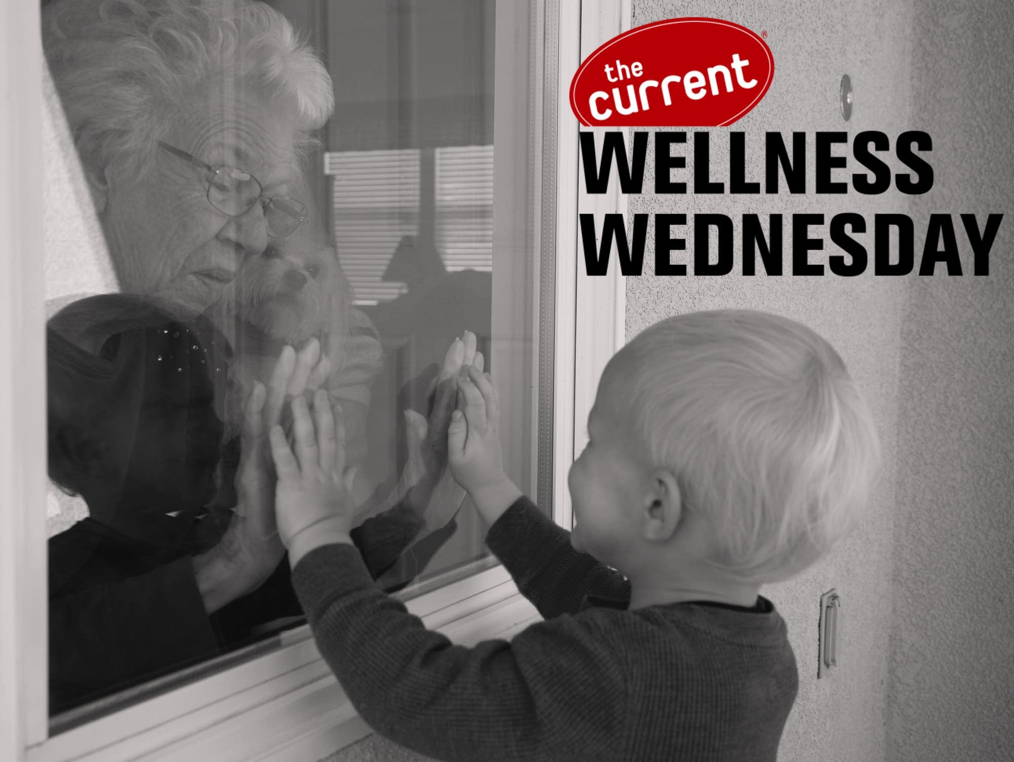 A child greets a senior through a closed window.