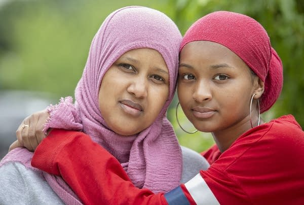 A teenager wearing a red hijab puts her arms around her mother.