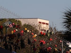 Flowers attached to a fence near Marjory Stoneman Douglas High School