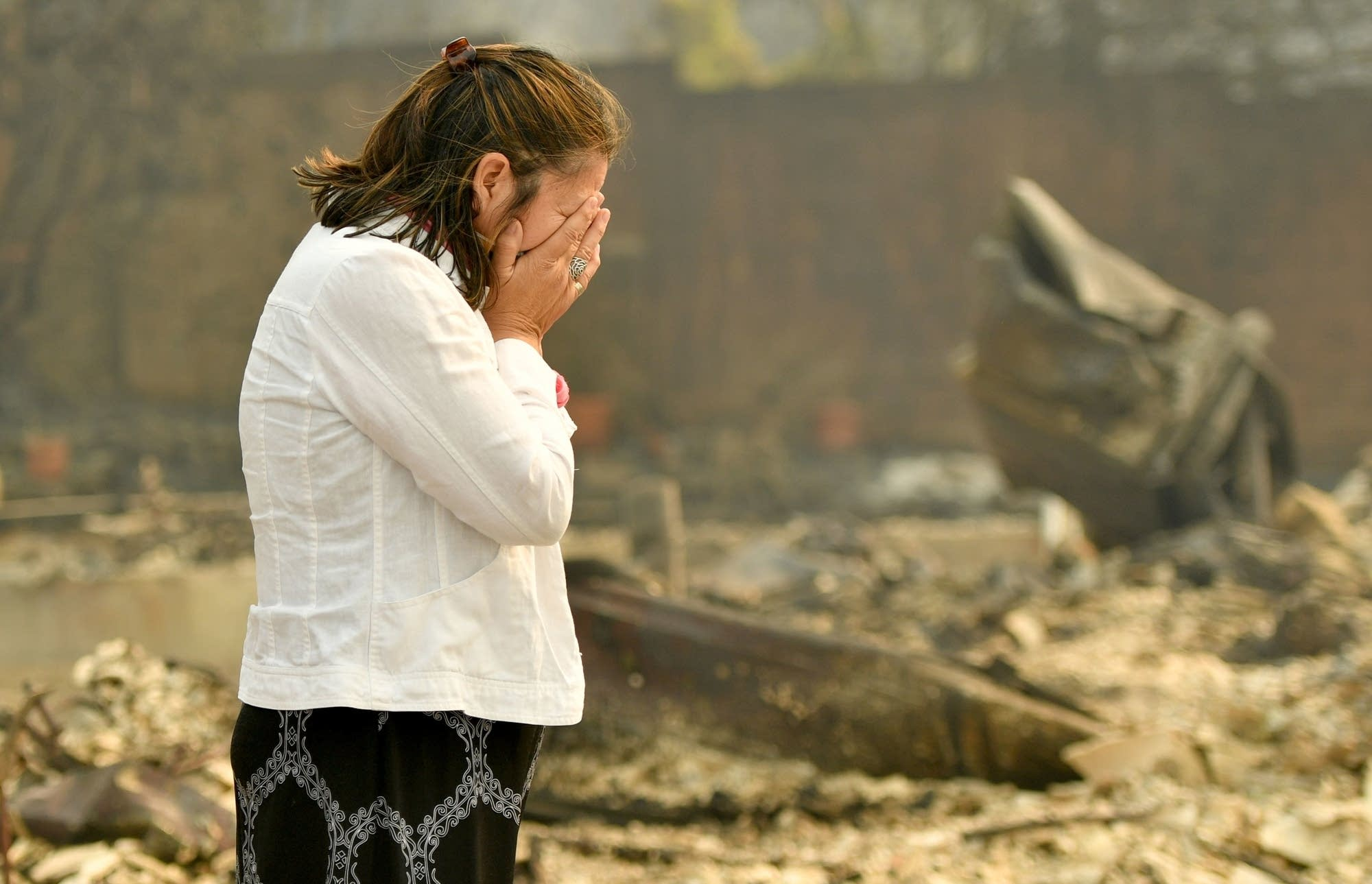 Martha Marquez looks over her burned home.