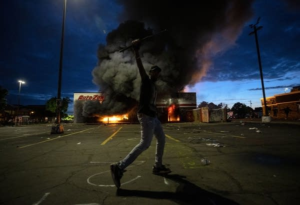 Man poses for photo outside burning business.