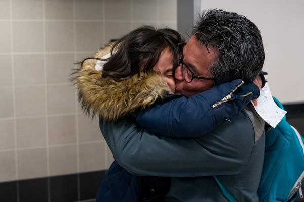 A man hugs and kisses his young daughter in an airport.