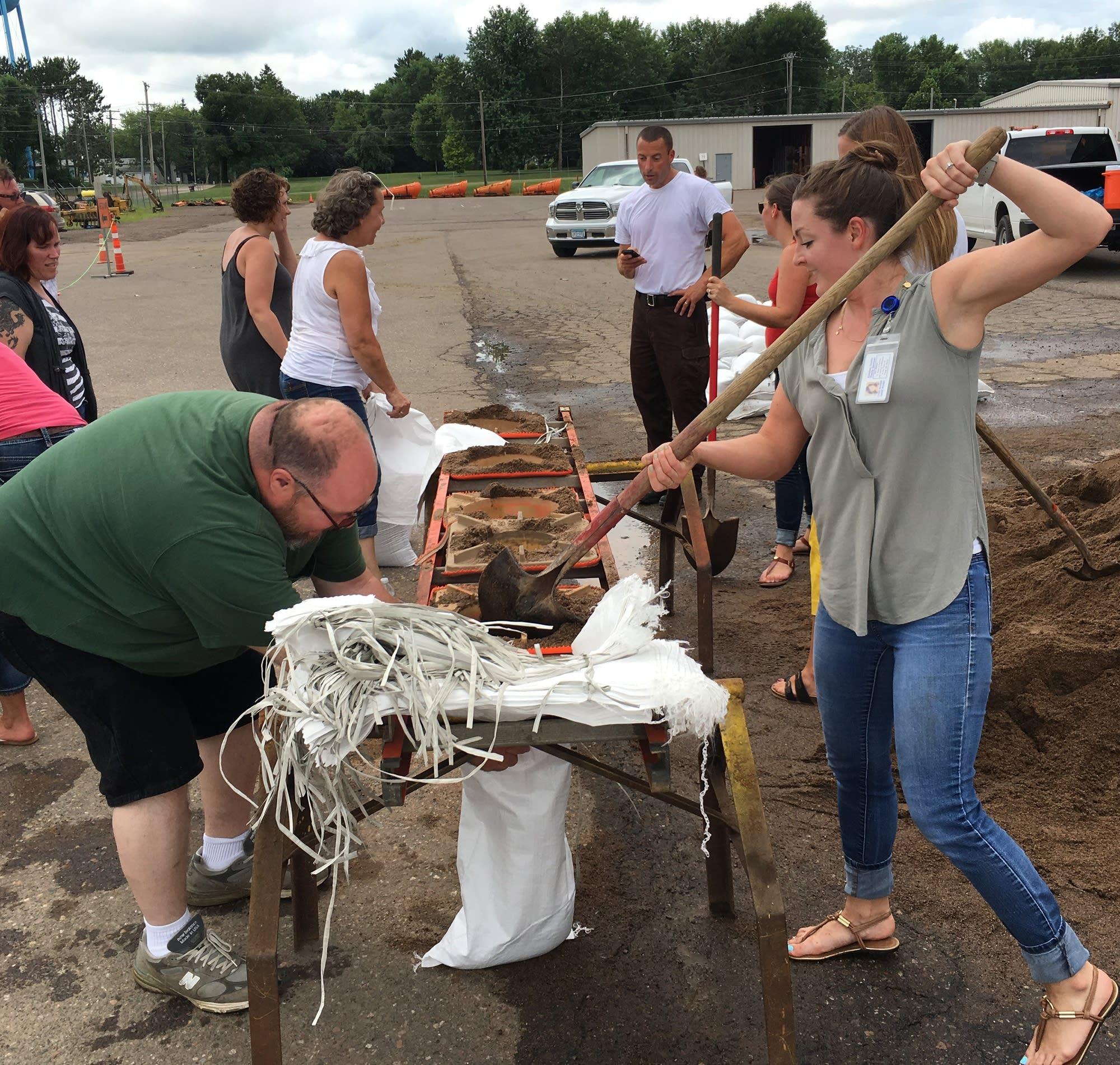 Sandbaggers fill bags in Mora after heavy overnight rains.