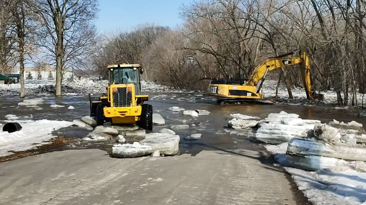 Crews work to remove an ice jam in Jordan, Minn.