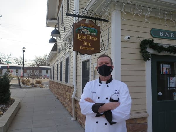 A man in a chef's shirt and face mask stands outside a business