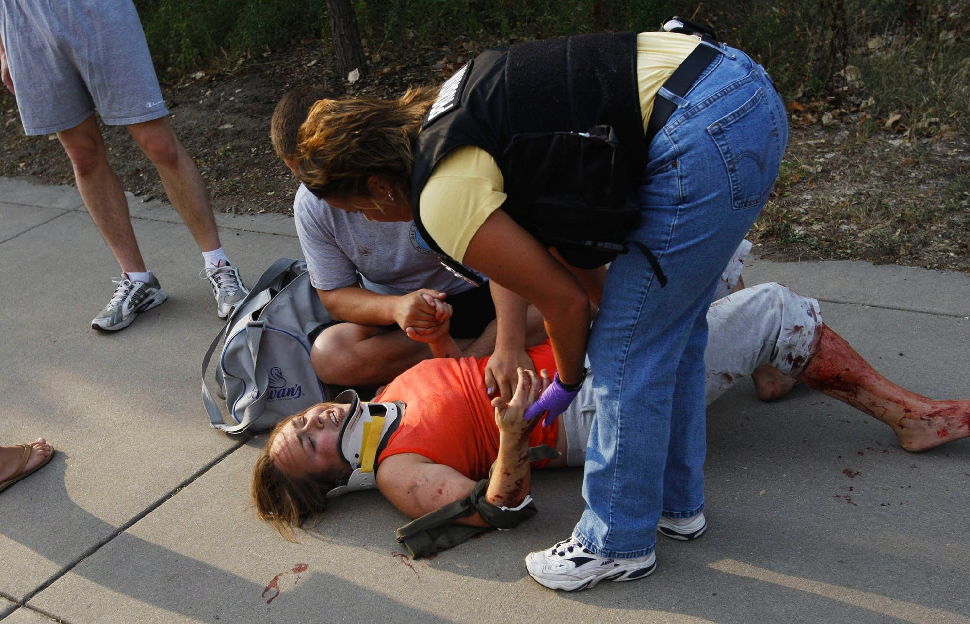 A rescue worker aids a victim after the Interstate 35W bridge collapsed.