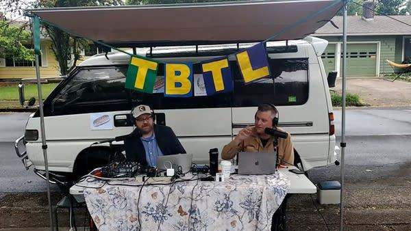 Luke and Andrew podcasting outside a minivan w/ TBTL Banner