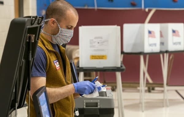 Poll worker Steve Hayes sanitizes pens at a polling place