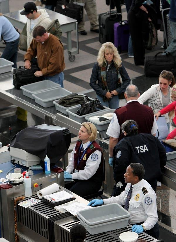 TSA officials conduct security screenings