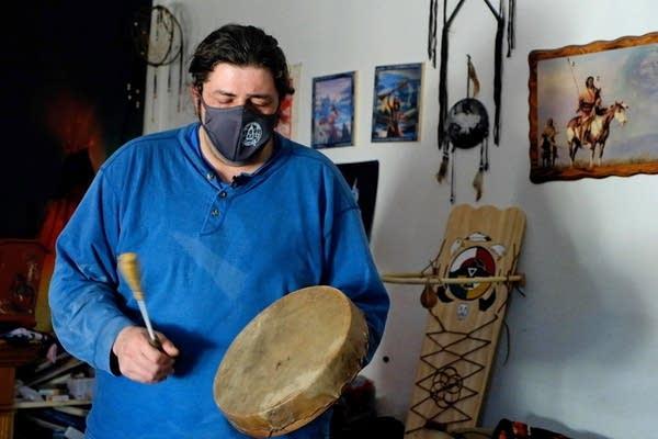 A man plays a traditional Ojibwe hand drum.