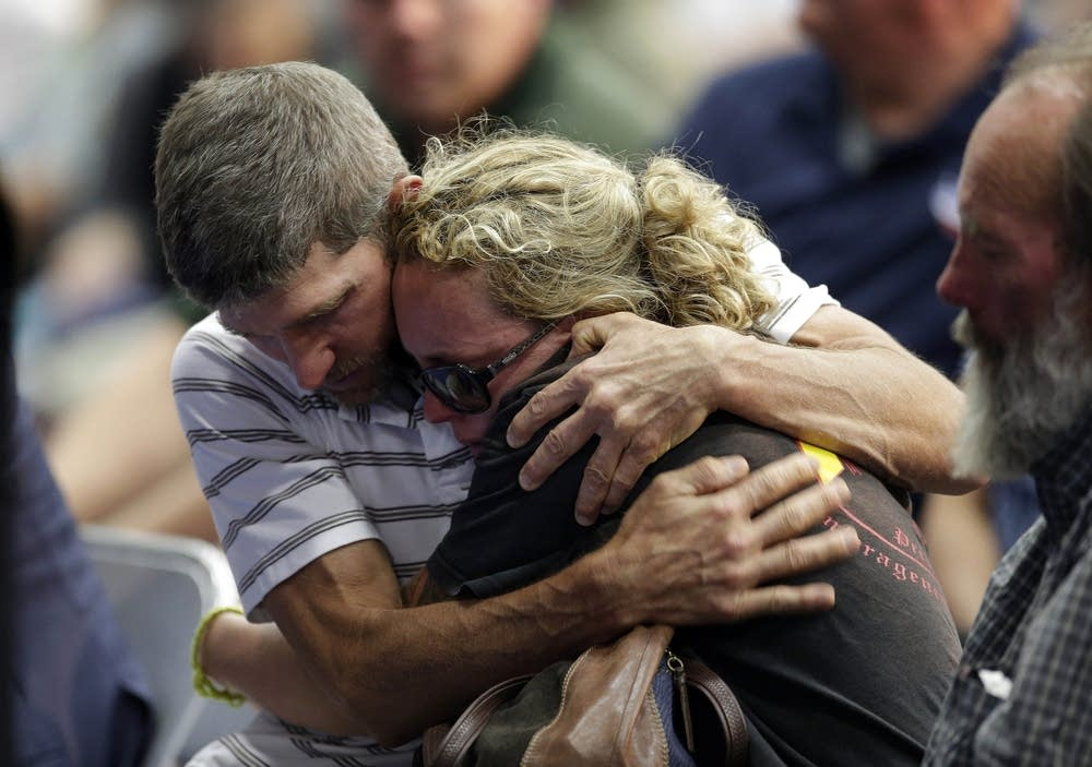 A couple embraces during a memorial service