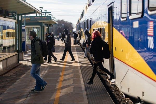 People step off of a train onto a platform.