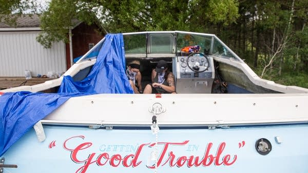 """Two activists sit inside a boat named """"Good Trouble."""""""