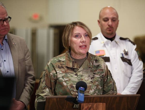 A woman in a uniform speaks in front of a microphone.