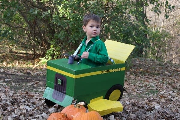 A child dressed in a box made to look like a tractor.