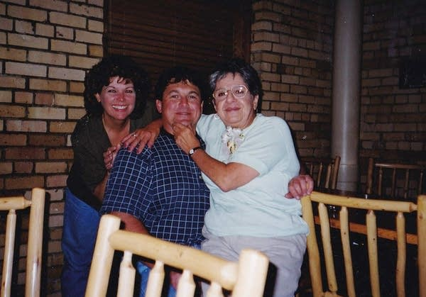 Three people posing for a photograph in a restaurant.