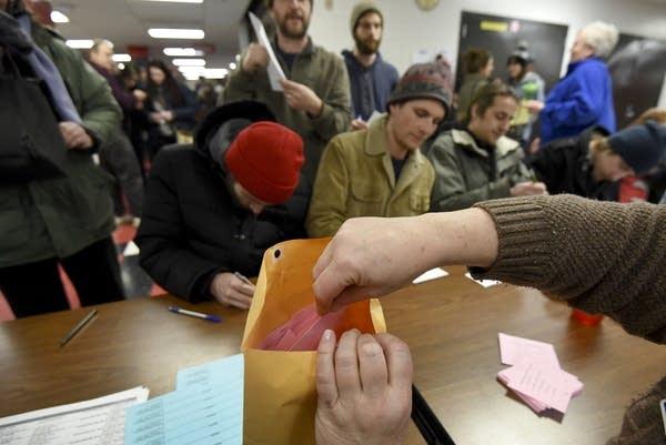 A caucus volunteer stuffs ballots.