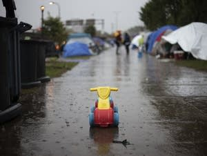 A toy rolled down the sidewalk in the rain at the homeless encampment