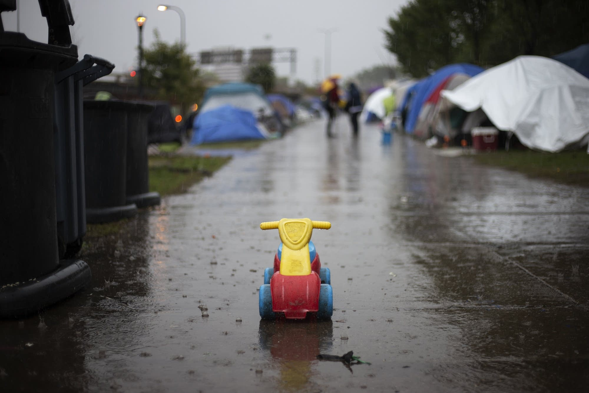 A toy rolls down the sidewalk in the rain at the homeless encampment