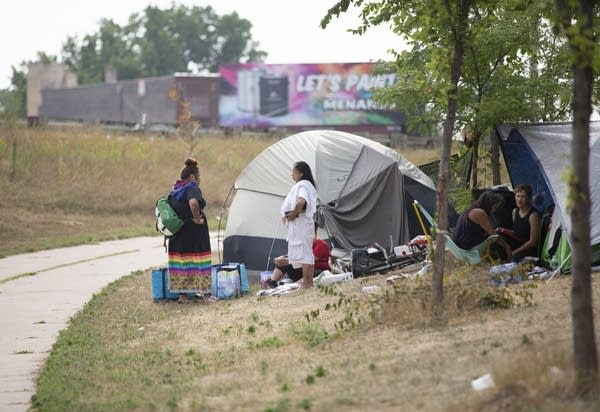 Residents of the homeless encampment stand outside of their tents.