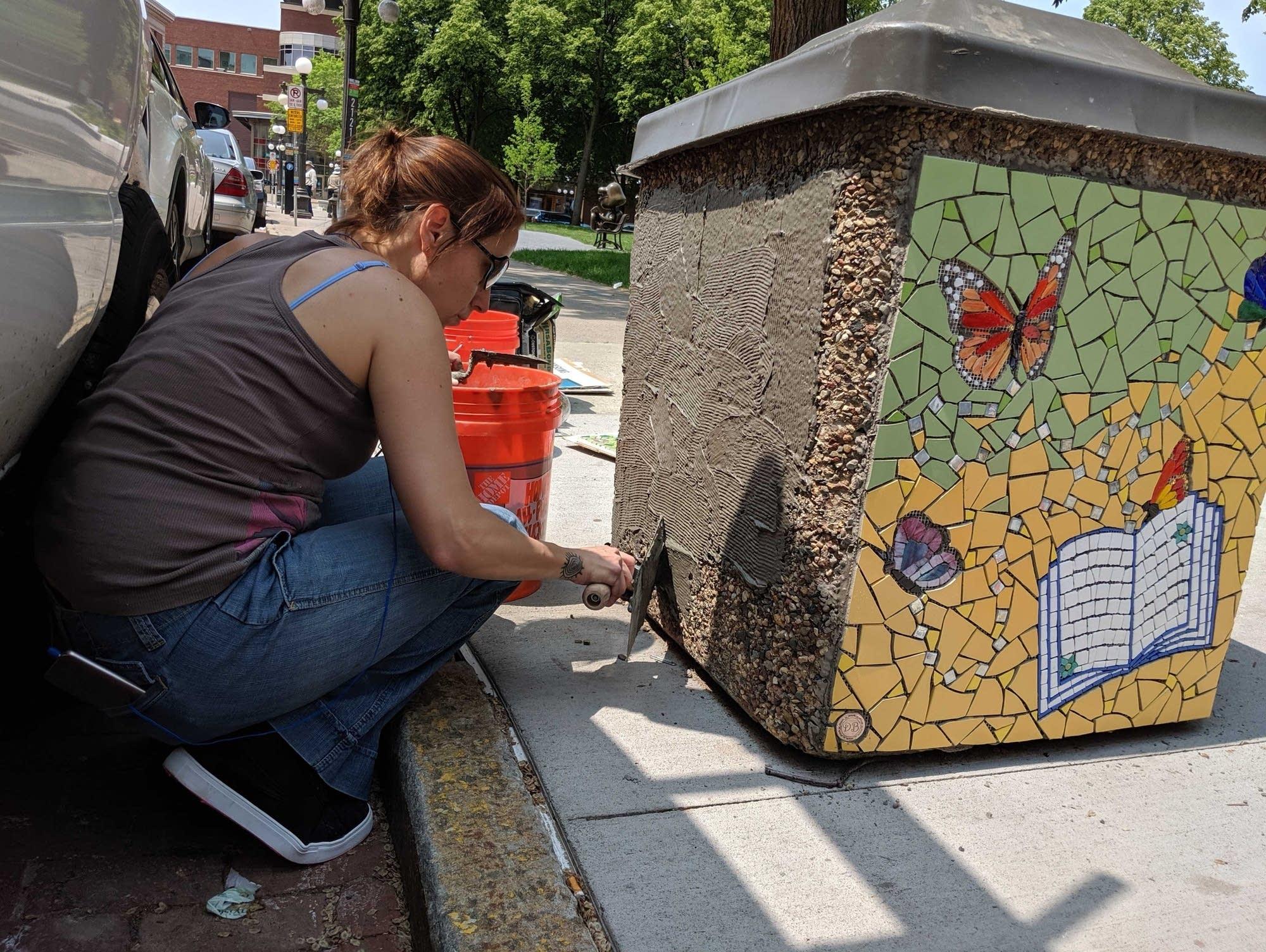 Mosaicist Daniela Bianchini applies mortar in Rice Park.