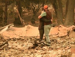 Chris and Nancy Brown embrace while looking over the remains of their home.