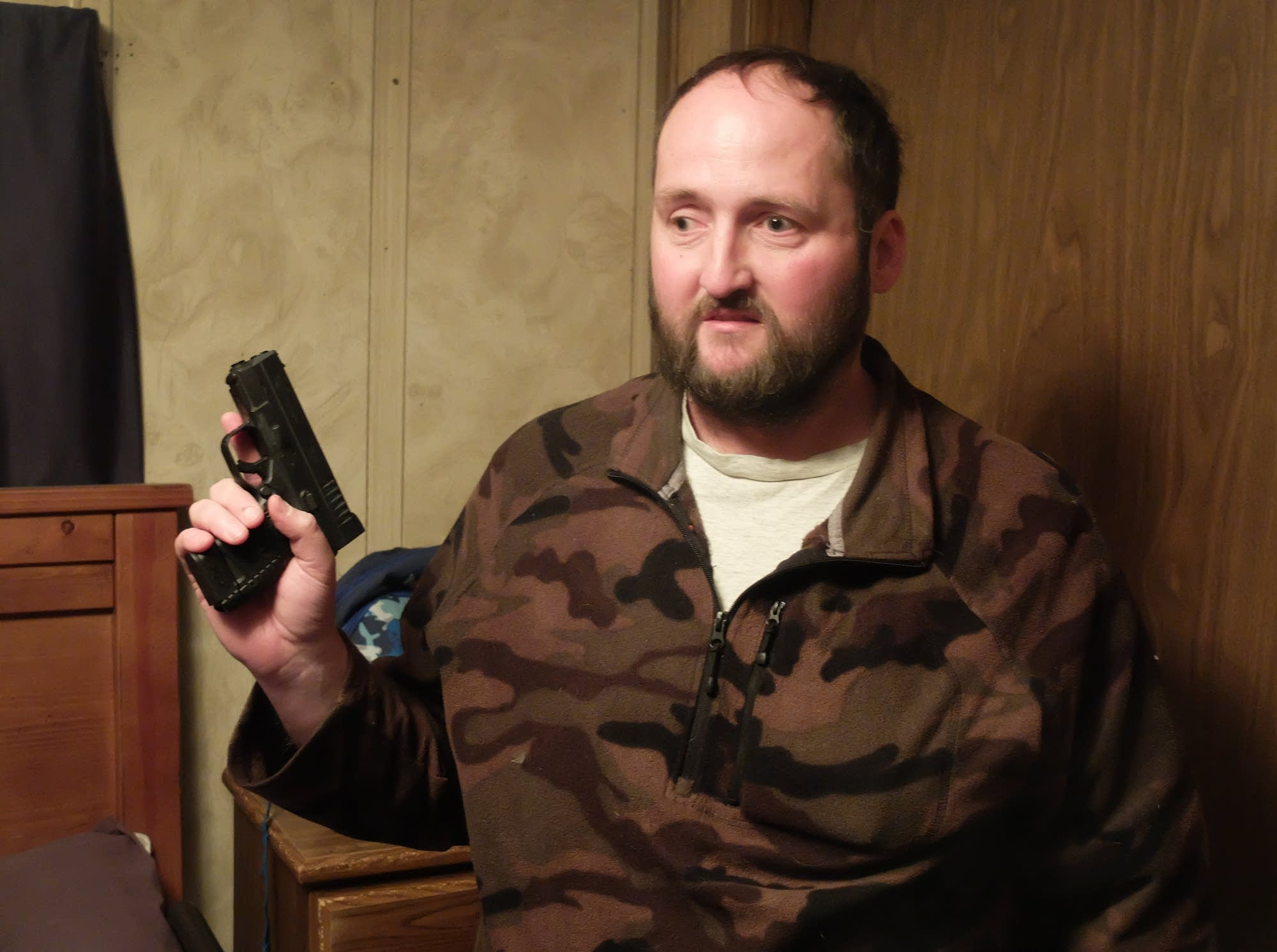 Carey McWilliams shows a loaded handgun he keeps in his Fargo home.