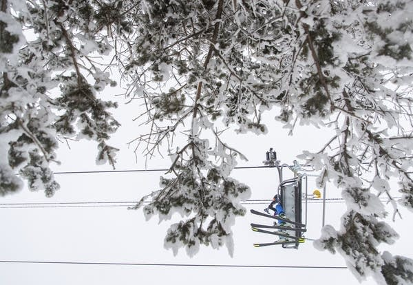 People on a ski lift seen through trees