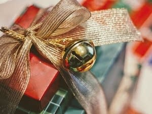 A bell decorates a wrapped present.