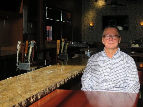 A man sits inside of an empty restaurant.